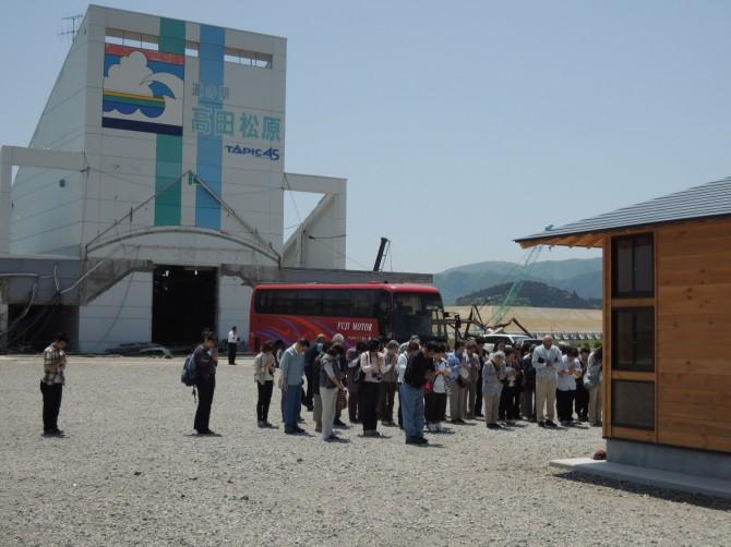 被災した道の駅の駐車場で黙祷する被災地バスツアーの観光客(陸前高田)